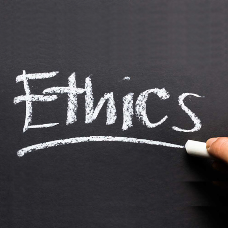 Hand writing Ethics topic on chalkboard